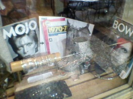 A non-mainstream store with David Bowie magazine covers as decoration.